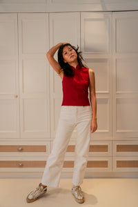 Model standing up wearing a red slit top with chinese buttons paired with white pants and white sneakers