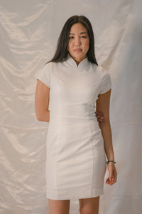 Model standing up wearing a white organic cotton mandarin collar cheongsam dress