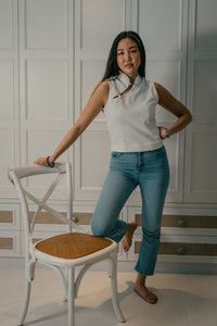 Model one leg on chair wearing a white organic cotton top with Chinese buttons paired with blue jeans