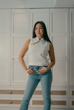 Load image into Gallery viewer, Model standing wearing a white organic cotton top with chinese buttons paired with blue jeans