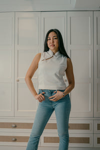Model standing wearing a white organic cotton top with chinese buttons paired with blue jeans