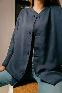 product shot of female model wearing navy blue mandarin collar jacket sitting down on chair with black shirt open