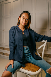 Female model wearing navy blue mandarin collar jacket sitting down on chair with black shirt open
