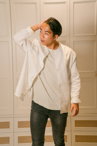 Model wearing mandarin scholar jacket with white t shirt brushing his hair