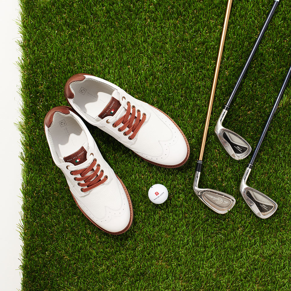 White Eldorado Shoe on grass with golf clubs and balls