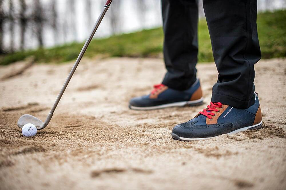 man wearing Camelot navy shoe on golf course