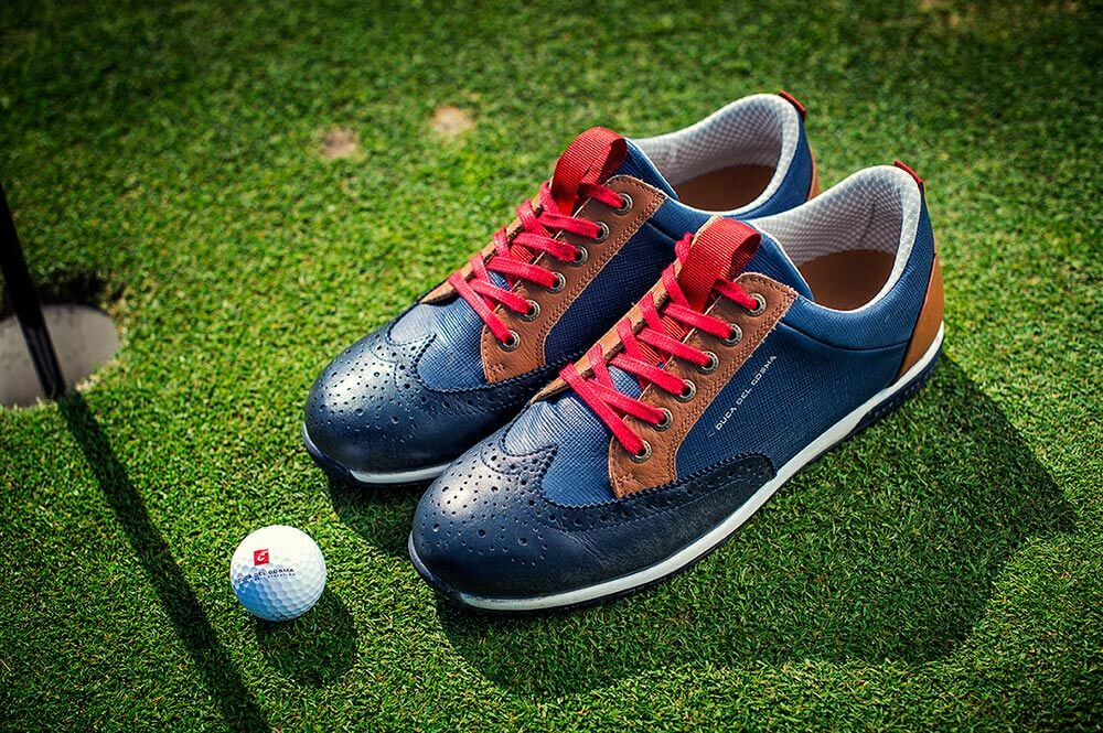 Camelot navy shoe on golf course with golf ball