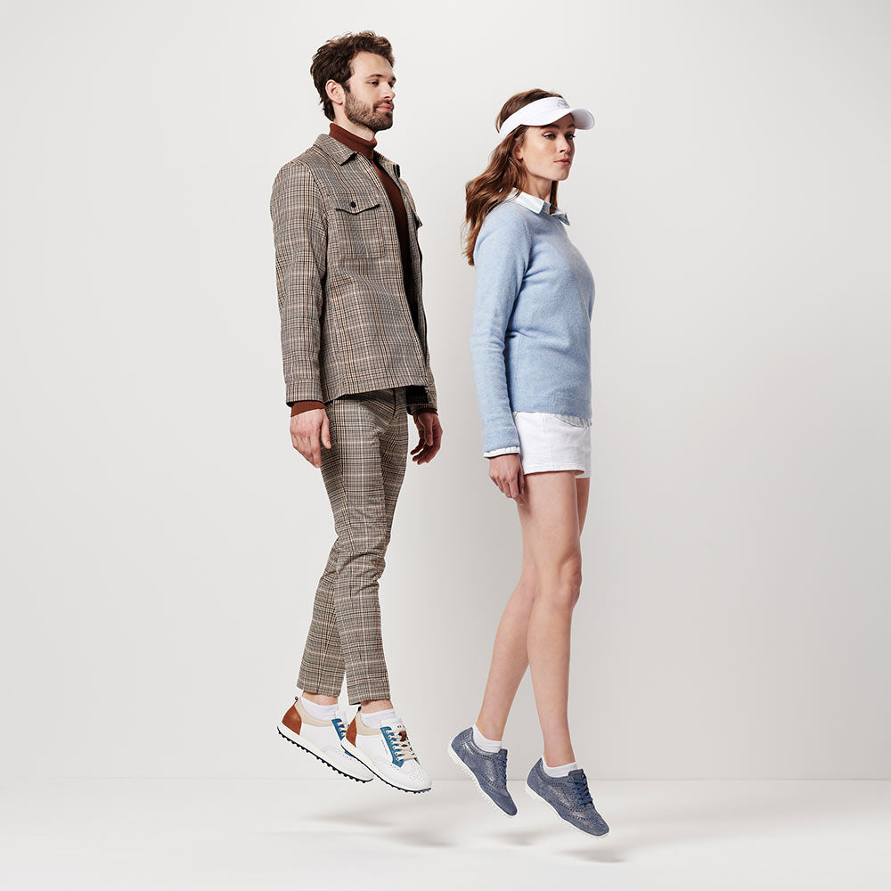 man and woman in Duca Del Cosma golf shoes jumping up