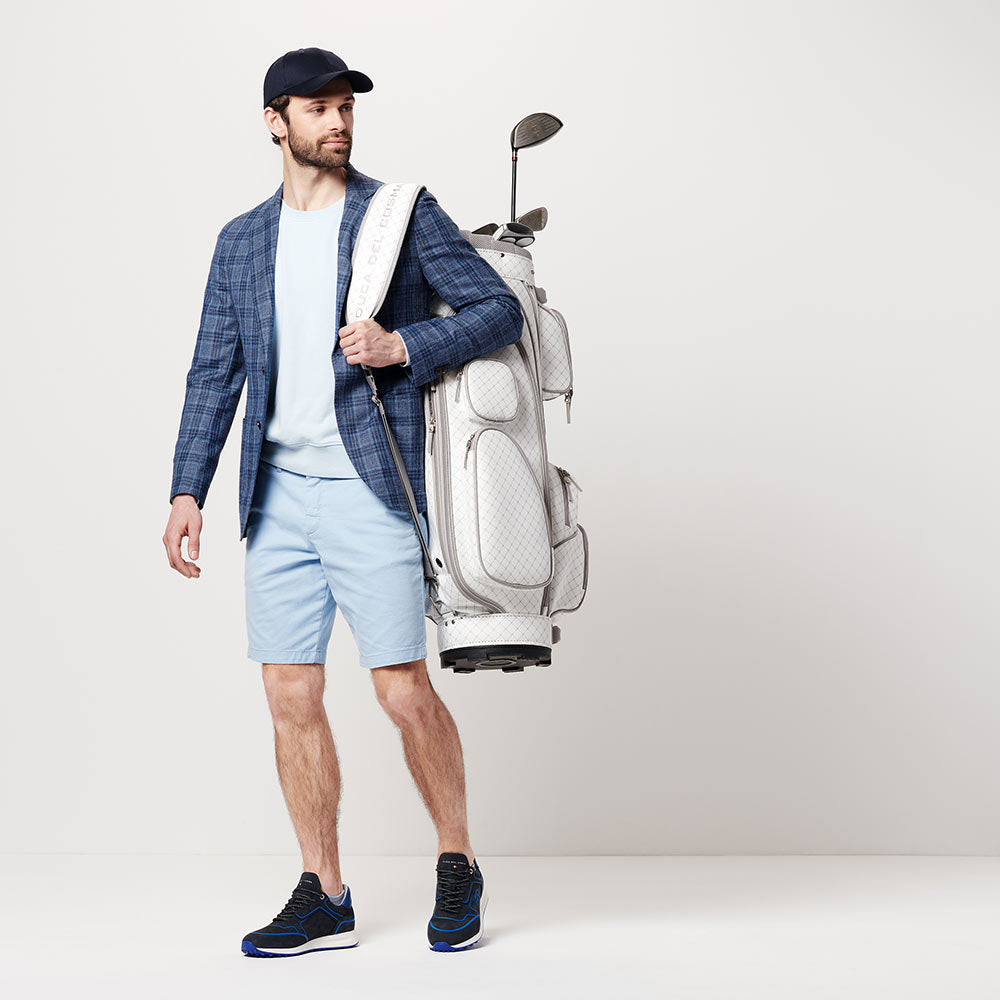 man wearing Flyer navy shoe with golf bag