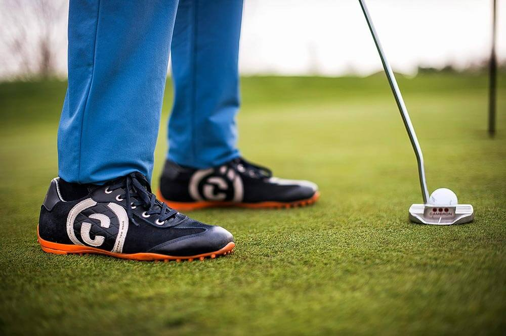 man putting wearing Kuba navy and orange shoe on golf course