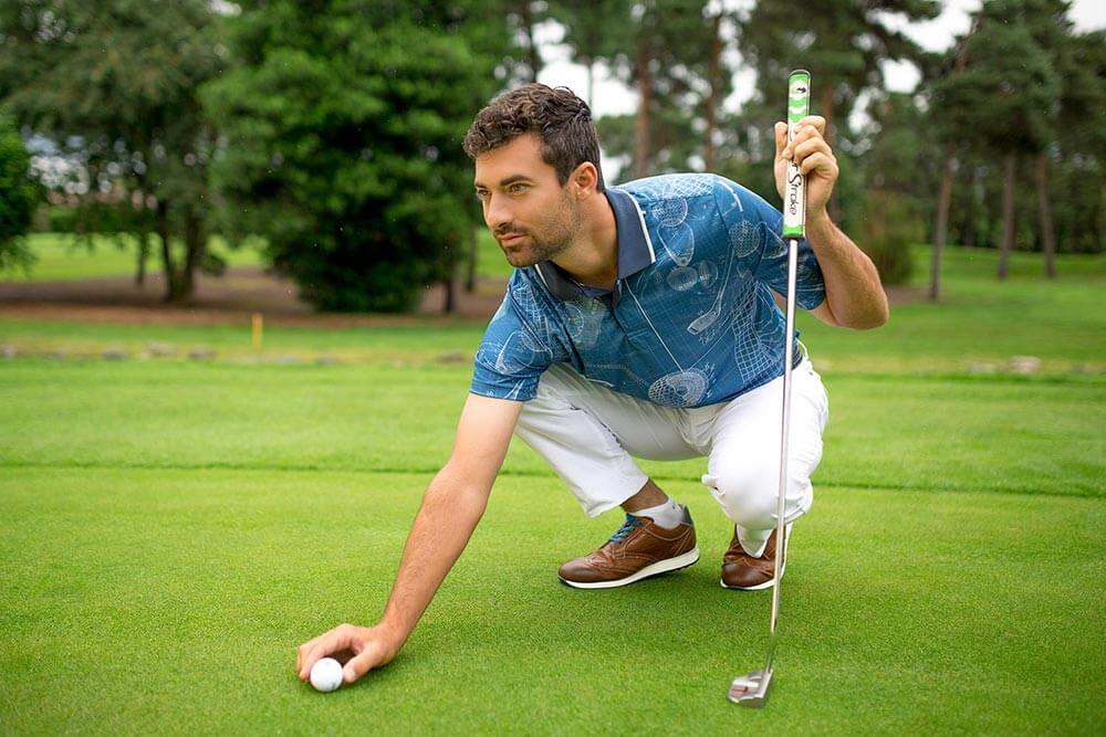 man placing golf ball wearing Duca del Cosma La Spezia II shoe on golf course
