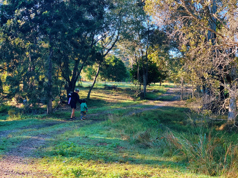 image shows natural bush valley with a path through the middle. woman carrying a baby on one hip and holding another childs hand
