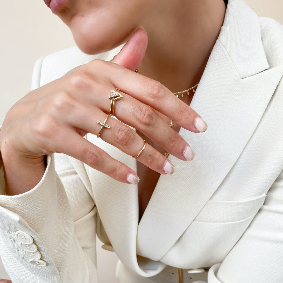 Gold crystal pave ring pack with midi ring, pave triangle interlink stack ring, stick ring and plain mini ring, jewellery on model.