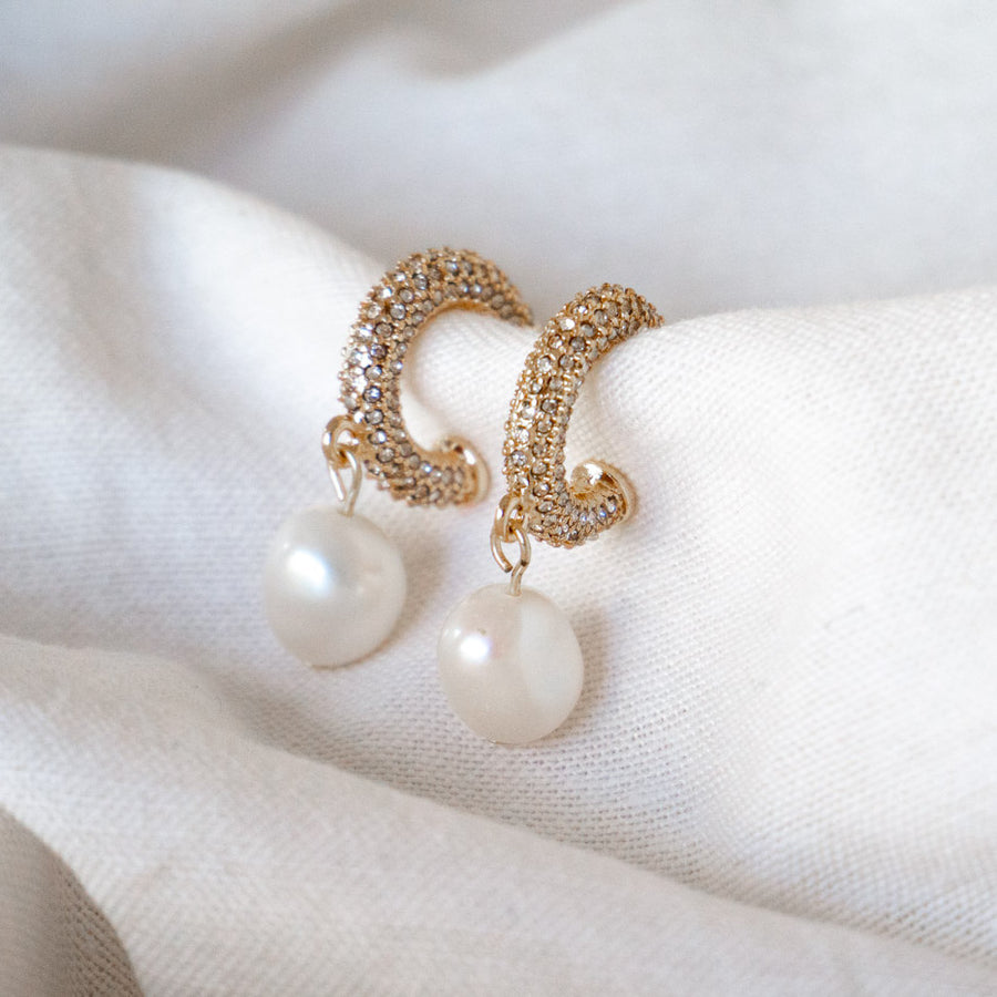 Gold crystal pave mini hoop with fresh water pearl charm drop earring on fabric still life