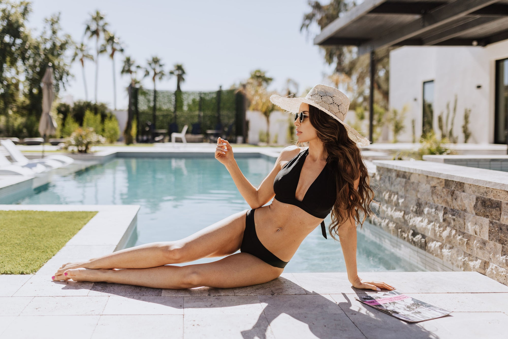 Thin brunette model posing by swimming pool wearing a black halter top bikini and matching bottoms with sunhat and sunglasses