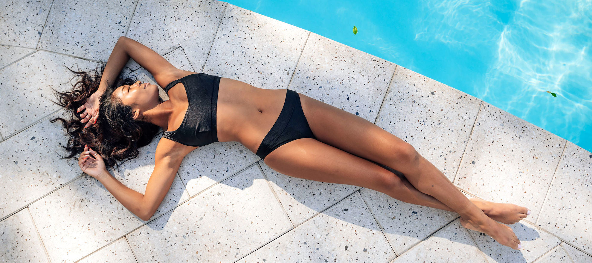 Slender woman lying on white stone tile next to a crystal clear swimming pool in a metallic black two piece bikini