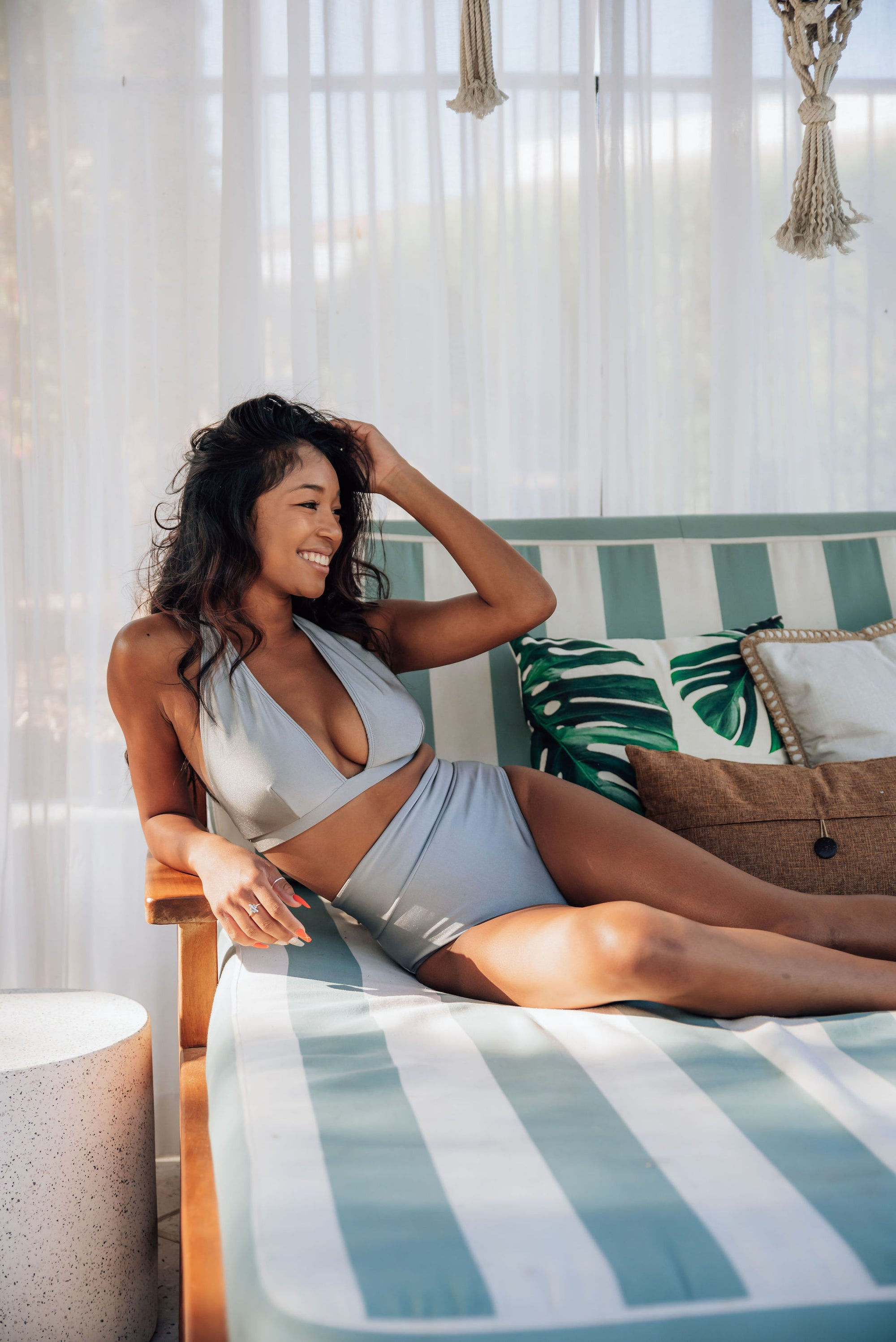 Woman gently playing with lightly curled black hair lying in boho style cabana wearing a silver metallic triangle top with coordinating high waisted bottoms