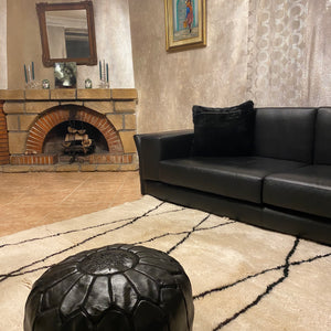 moroccan white wool rug in a living room with a black leather pouf