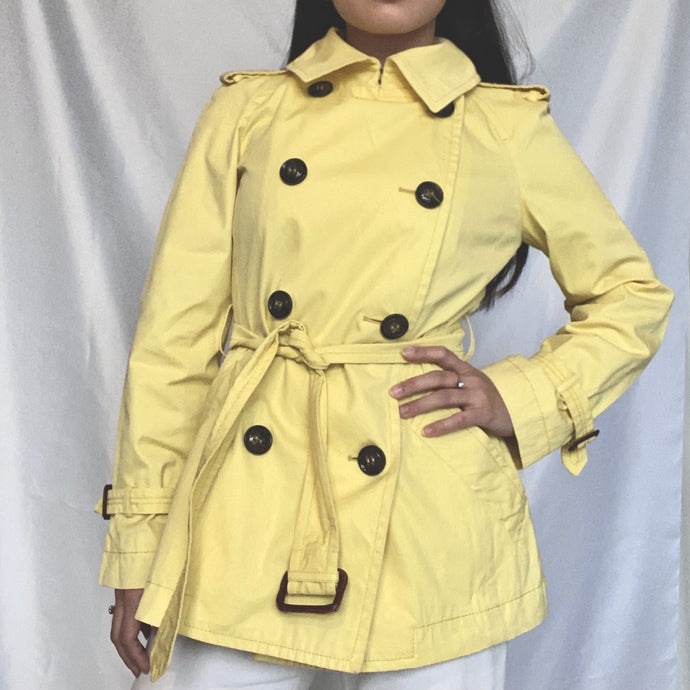 This is a Max Mara Vintage Trenchcoat in the colour Pastel Yellow. It is available on thrifted-vintage.com