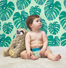 Baby with a toy sloth wearing rainforest design diaper