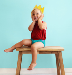 Toddler sitting on a bench wearing a crown smiling
