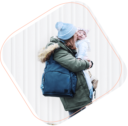 Mom holding and giving baby a kiss outdoors wearing Bambino Mio diaper bag