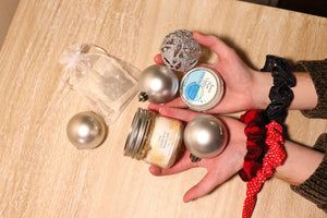 Hands holding ornaments and self care products, candles, and lotions.