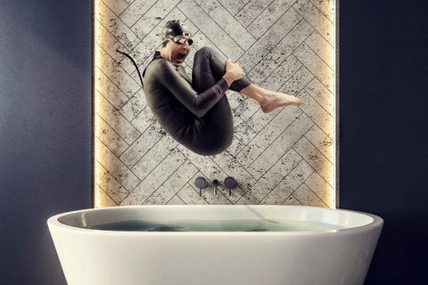 Triathlete Laura Siddall bombs into a bath wearing a Deboer wetsuit
