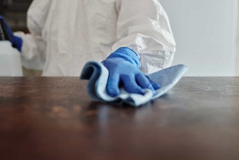 Person cleaning an office desk with a microfibre cloth