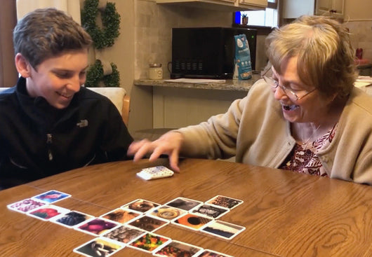 Grandmother and son playing OuiSi. OuiSi is great for multigenerational creativity, conversation and play.