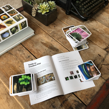 Load image into Gallery viewer, OuiSi guidebook open on coffee table, with cards all around.