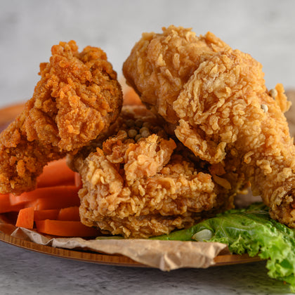 Deep fried chicken resting on a plate with carrots and lettuce