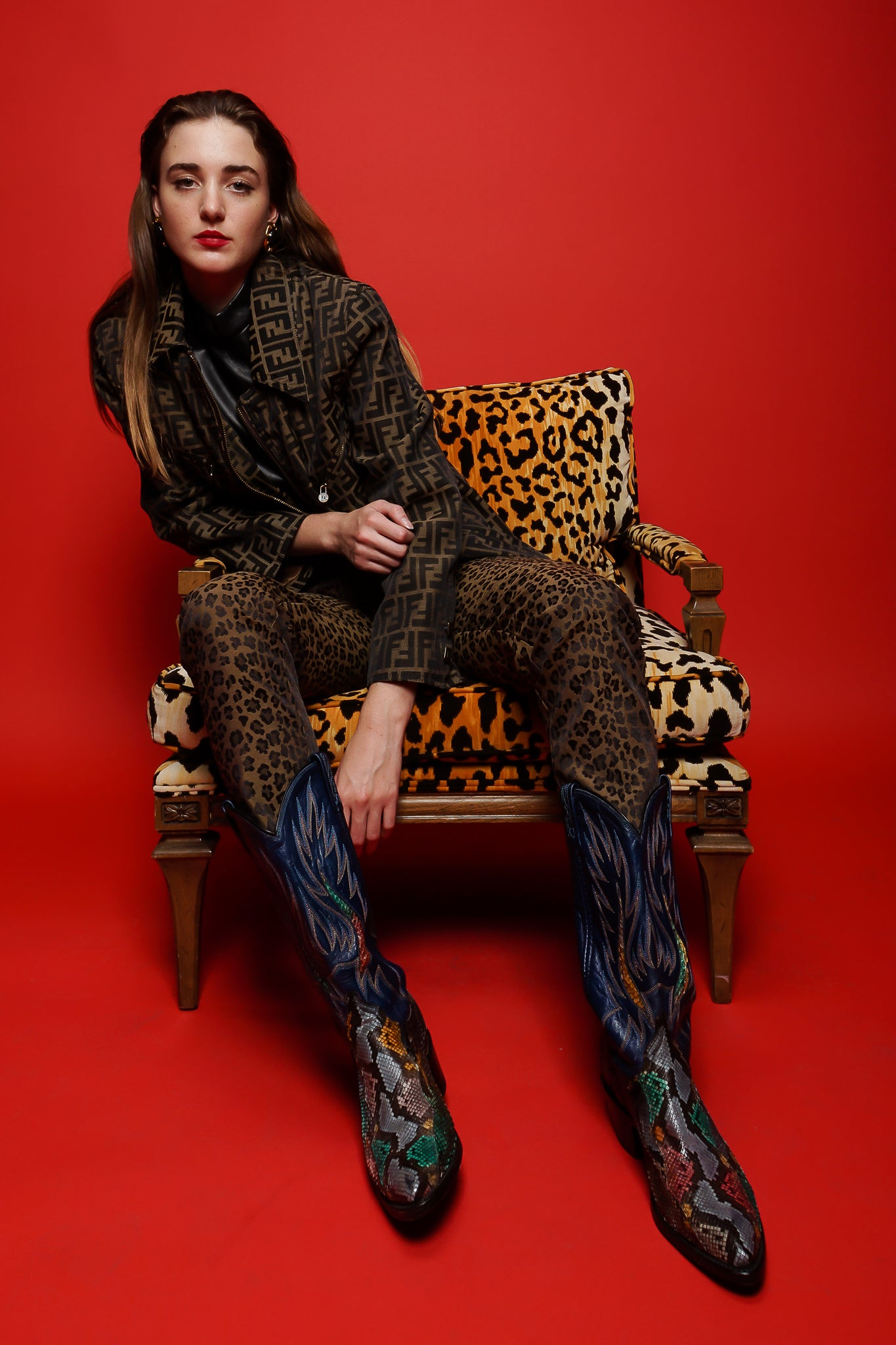 Girl in Fendi Zucca twill zip jacket & animal pant in animal chair on red at Recess Los Angeles