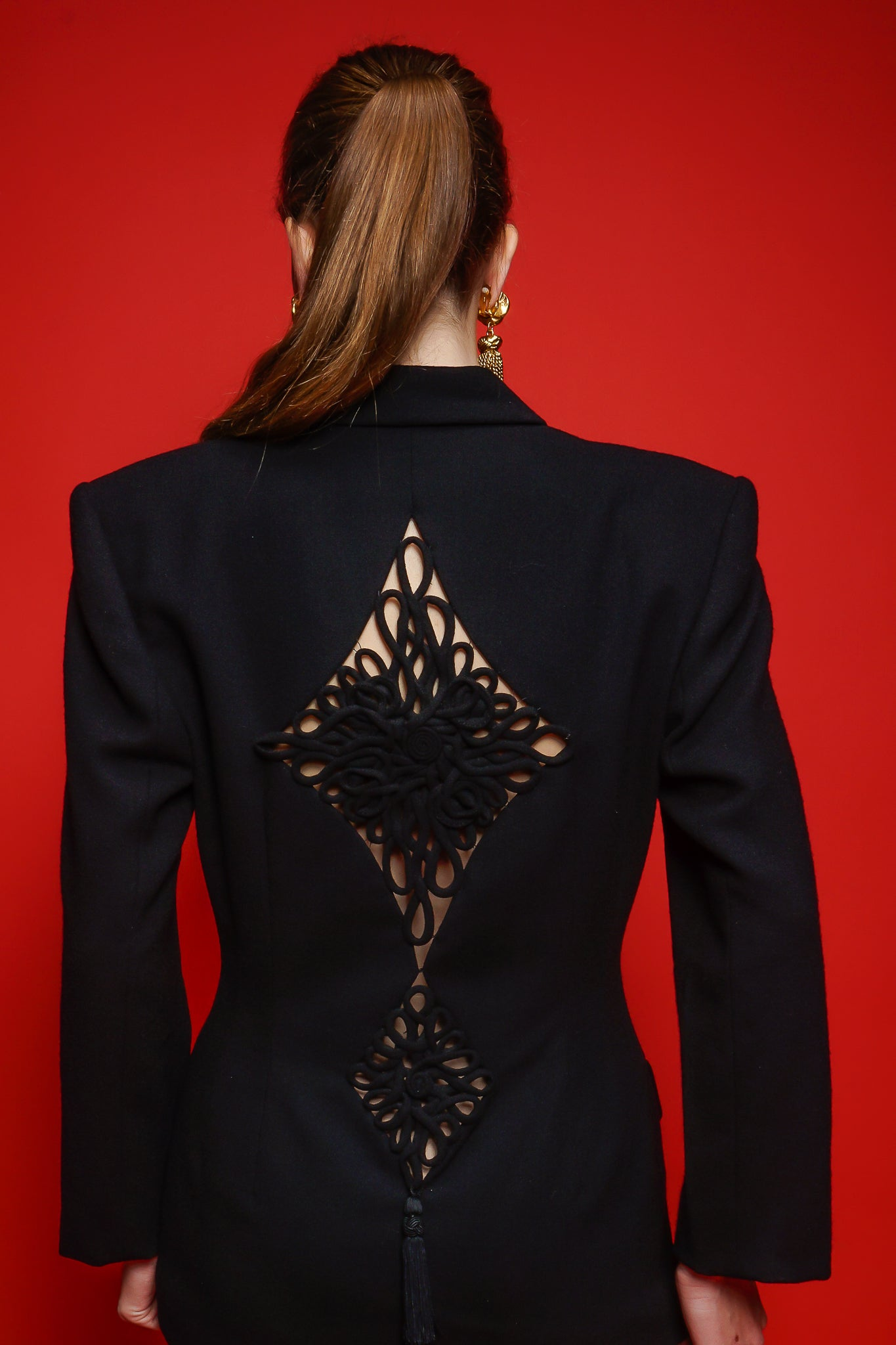Girl in black M.Yoko frog tassel cutout suit in on red background at Recess Los Angeles