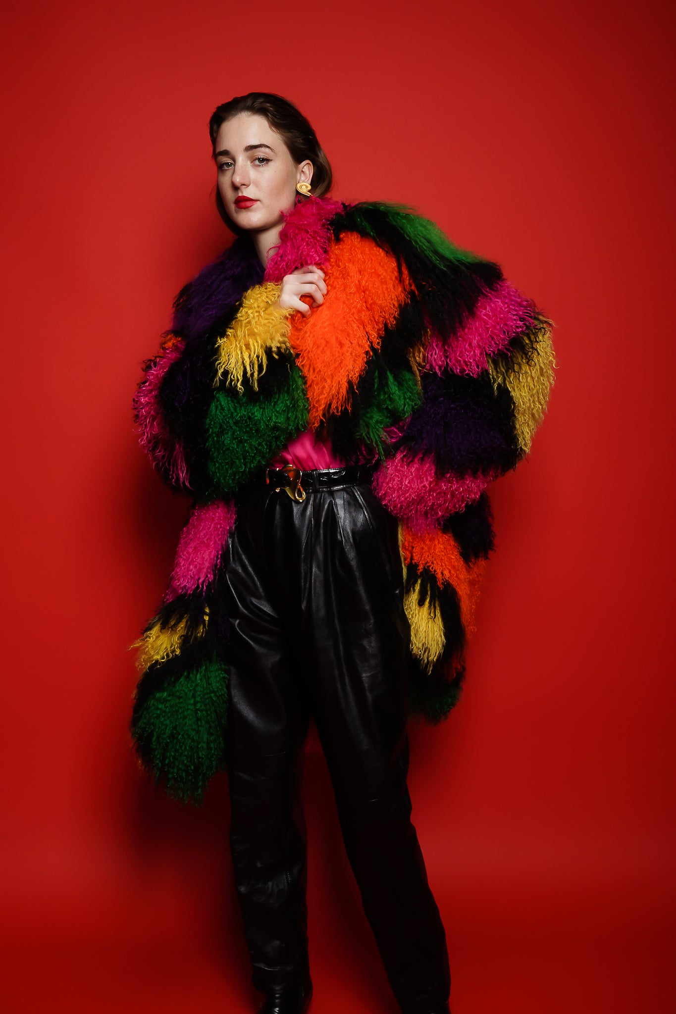Girl in Neiman Marcus rainbow Mongolian fur & YSL leather pant on red at Recess Los Angeles