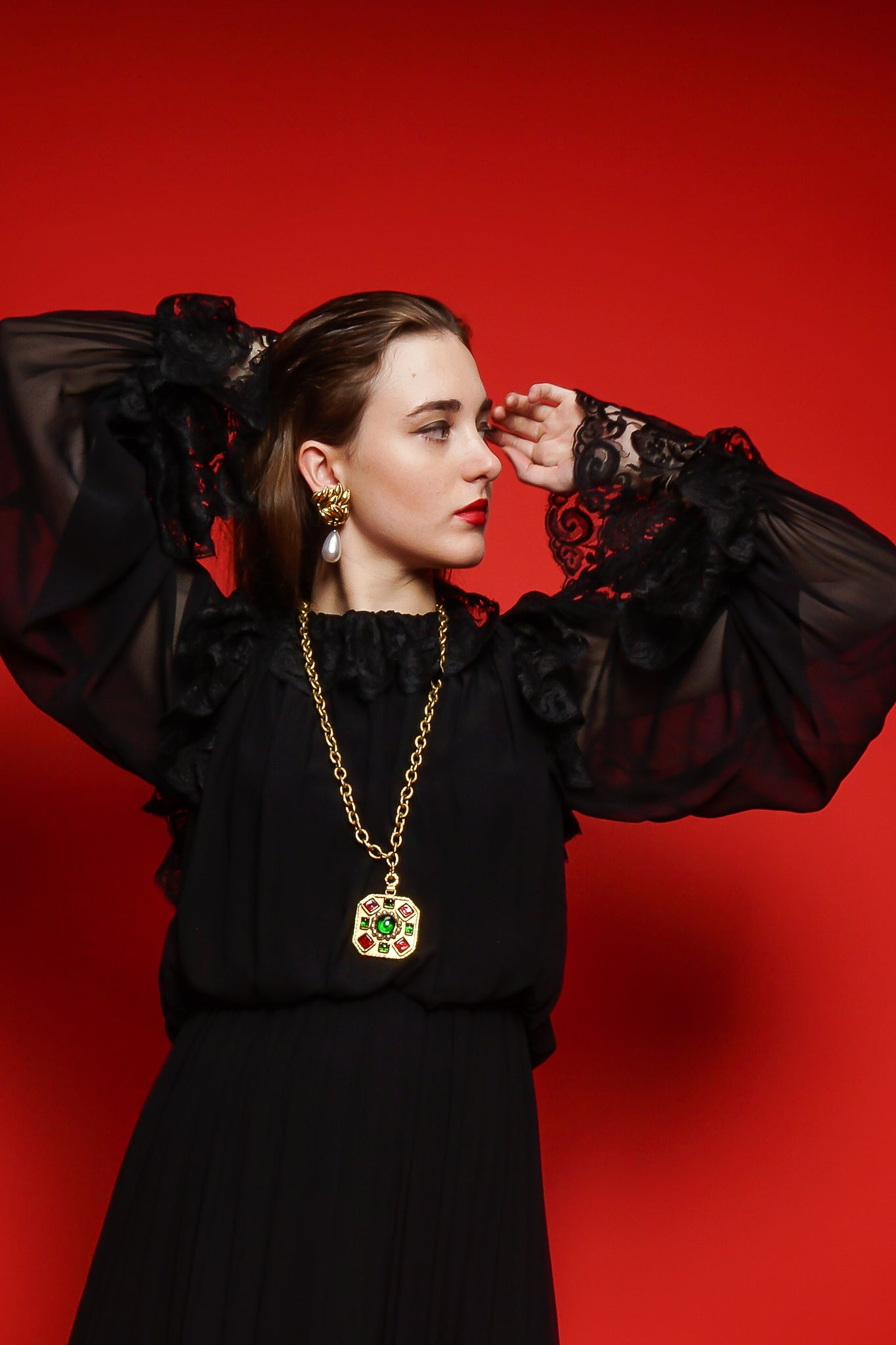 Girl in black Richilene lace dress & Chanel necklace on red background at Recess Los Angeles
