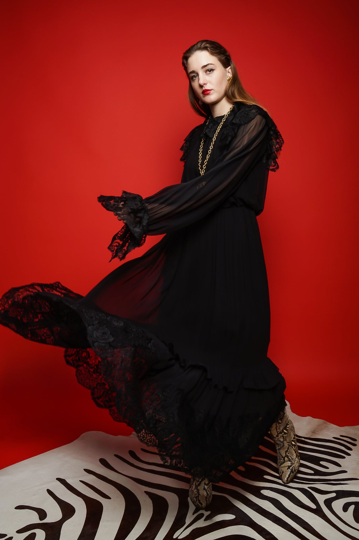 Girl in black Richilene lace trim dress on red background zebra rug at Recess Los Angeles
