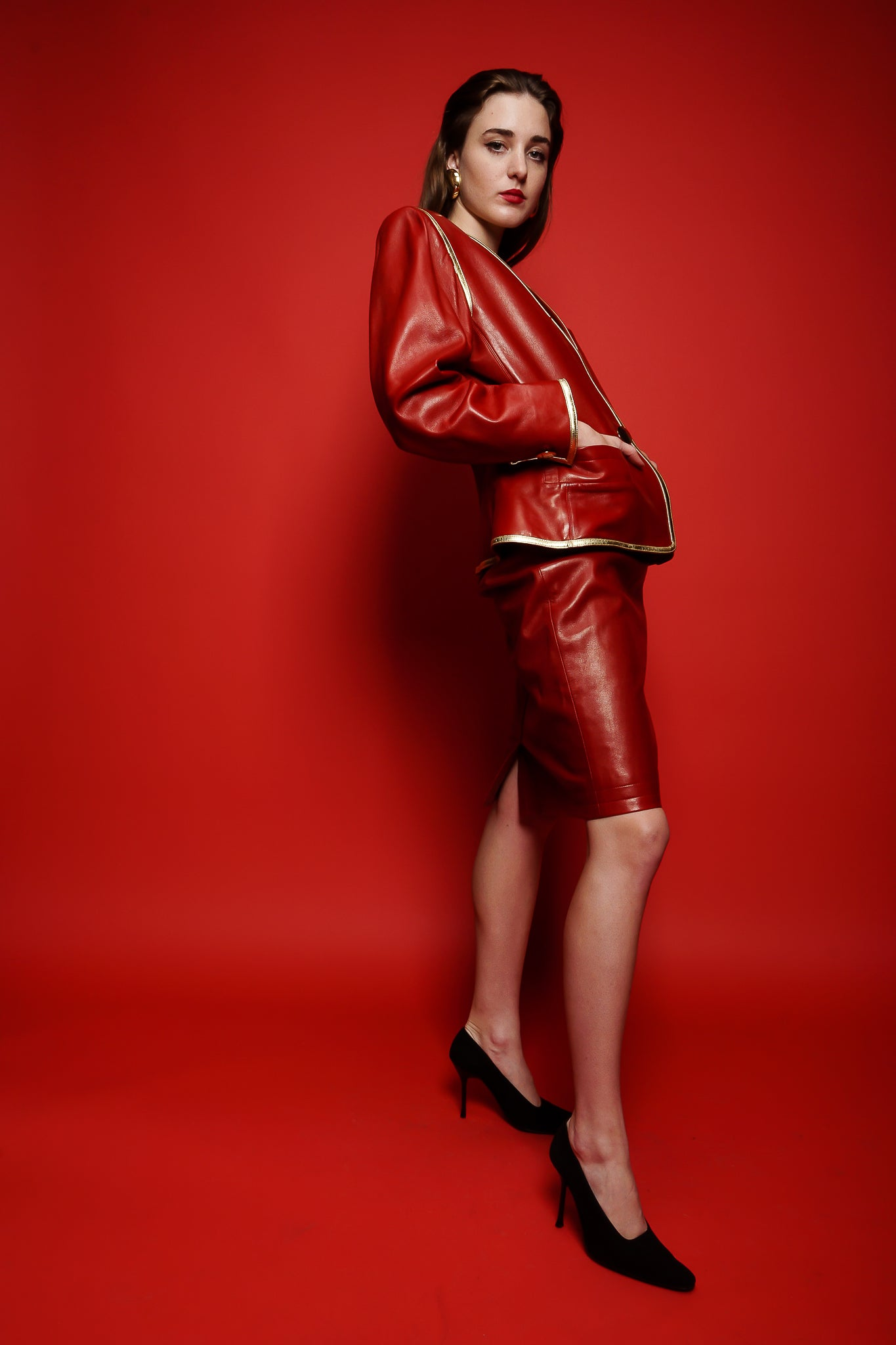 Girl in red vintage Yves Saint Laurent leather suit on red background at Recess Los Angeles
