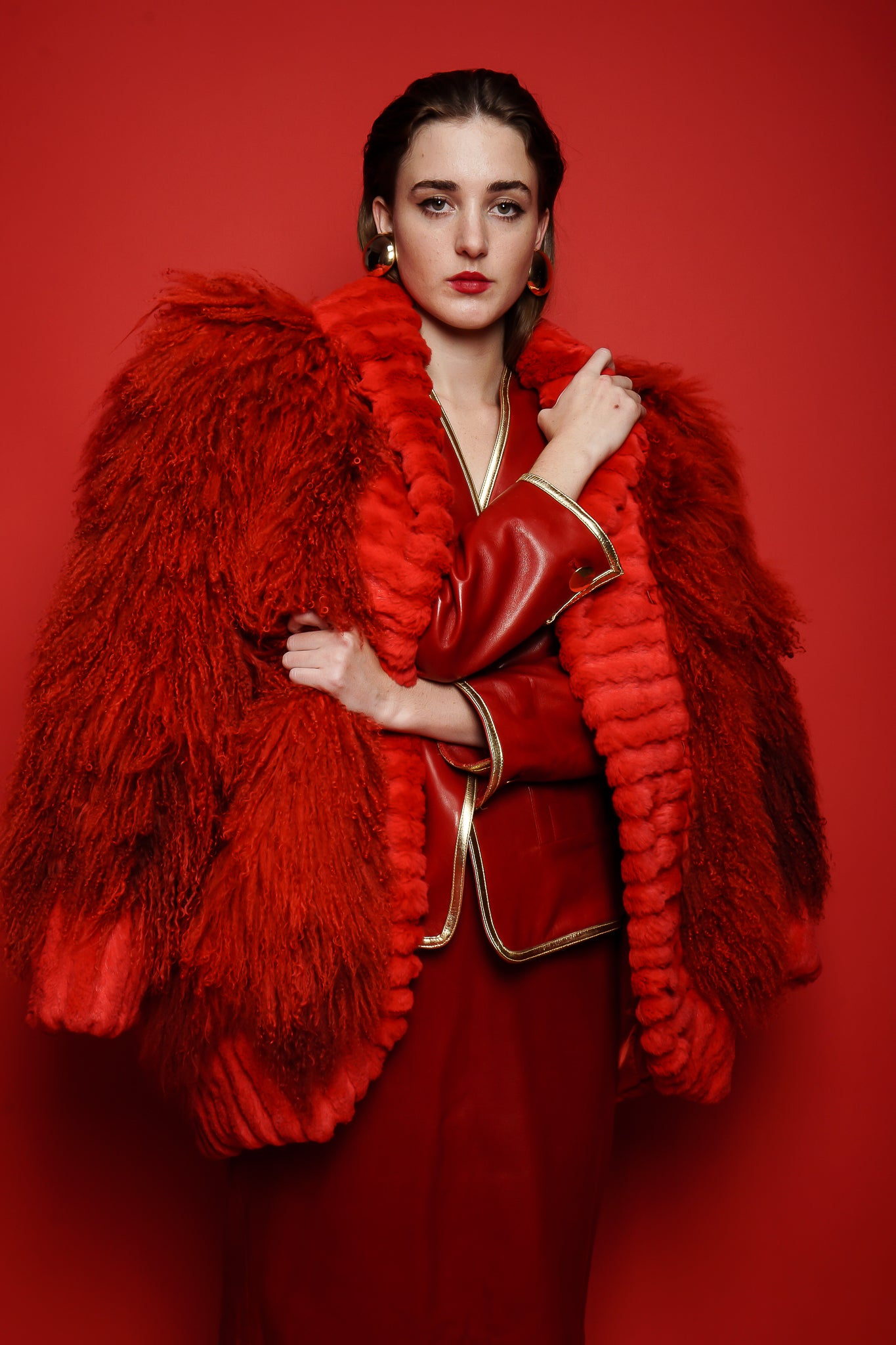 Girl in red vintage Yves Saint Laurent leather suit and Mongolian fur on red at Recess Los Angeles