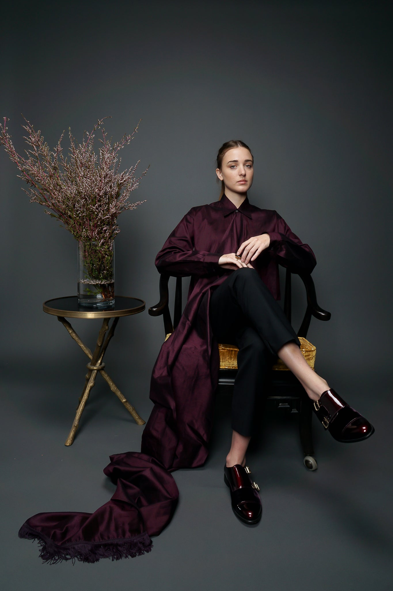 Girl wearing maroon Callaghan scarf top sitting in chair at Recess LA Designer Vintage Consignment