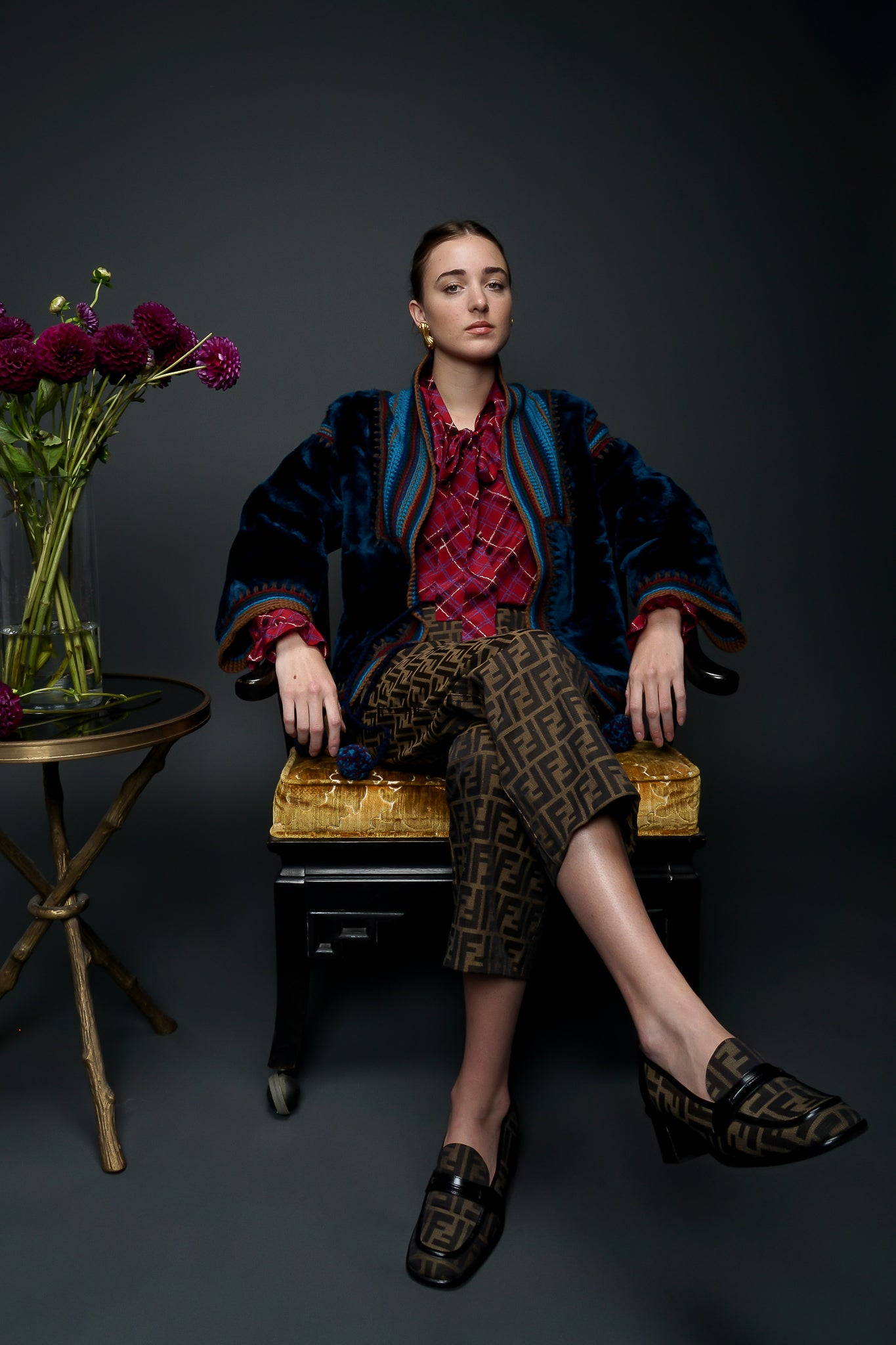 Recess Designer Vintage Consignment Girl wearing blue faur fur & fendi zucca pant sitting in chair