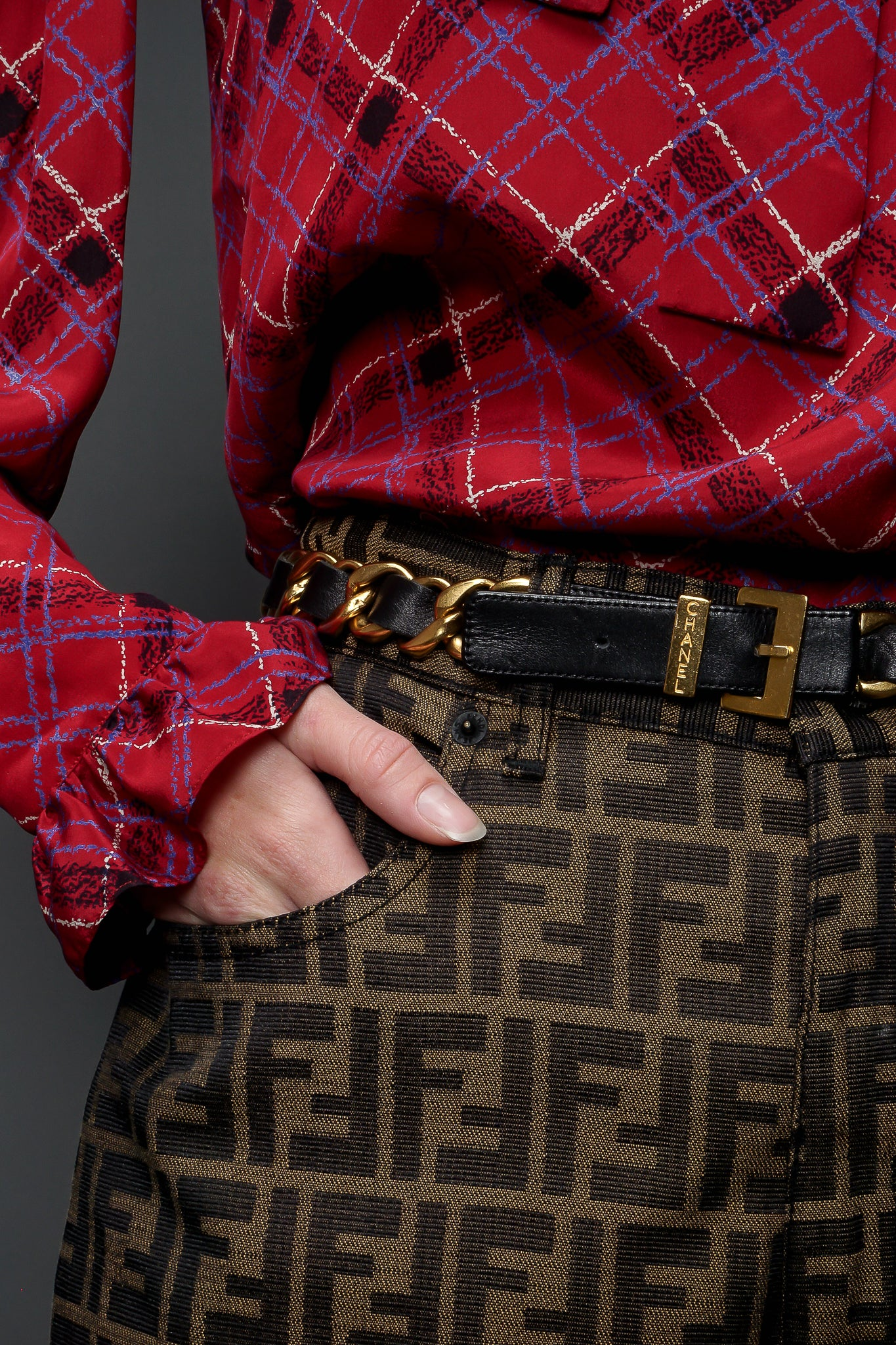 Recess Designer Vintage Consignment Girl wearing pink paid blouse & fendi zucca pant & chanel belt