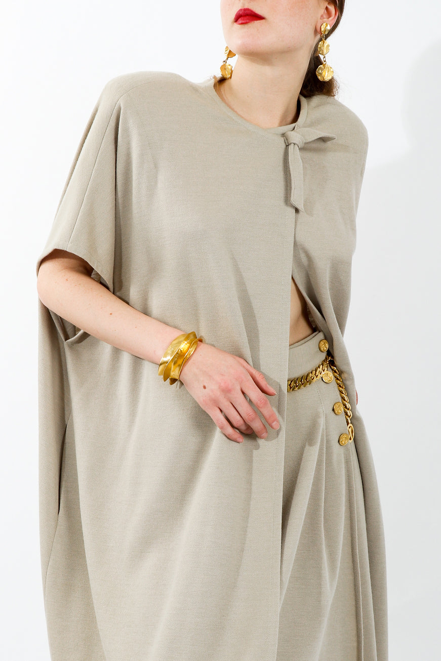 Girl wearing beige Sonia Rykiel cape and shorts set with gold earrings bracelet and belt
