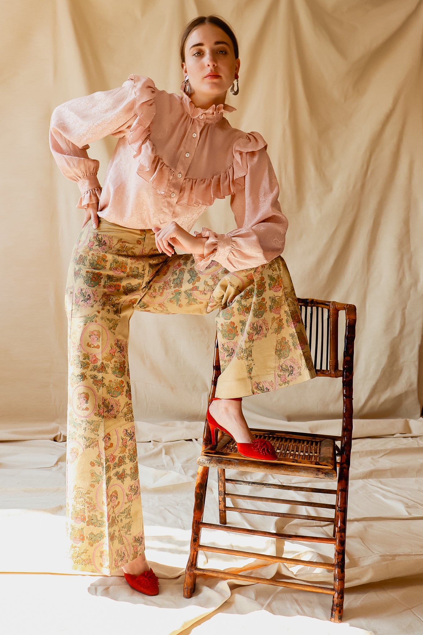 Recess Vintage Consignment LA Girl stepping on chair in YSL Blouse & Painted Suede Pants