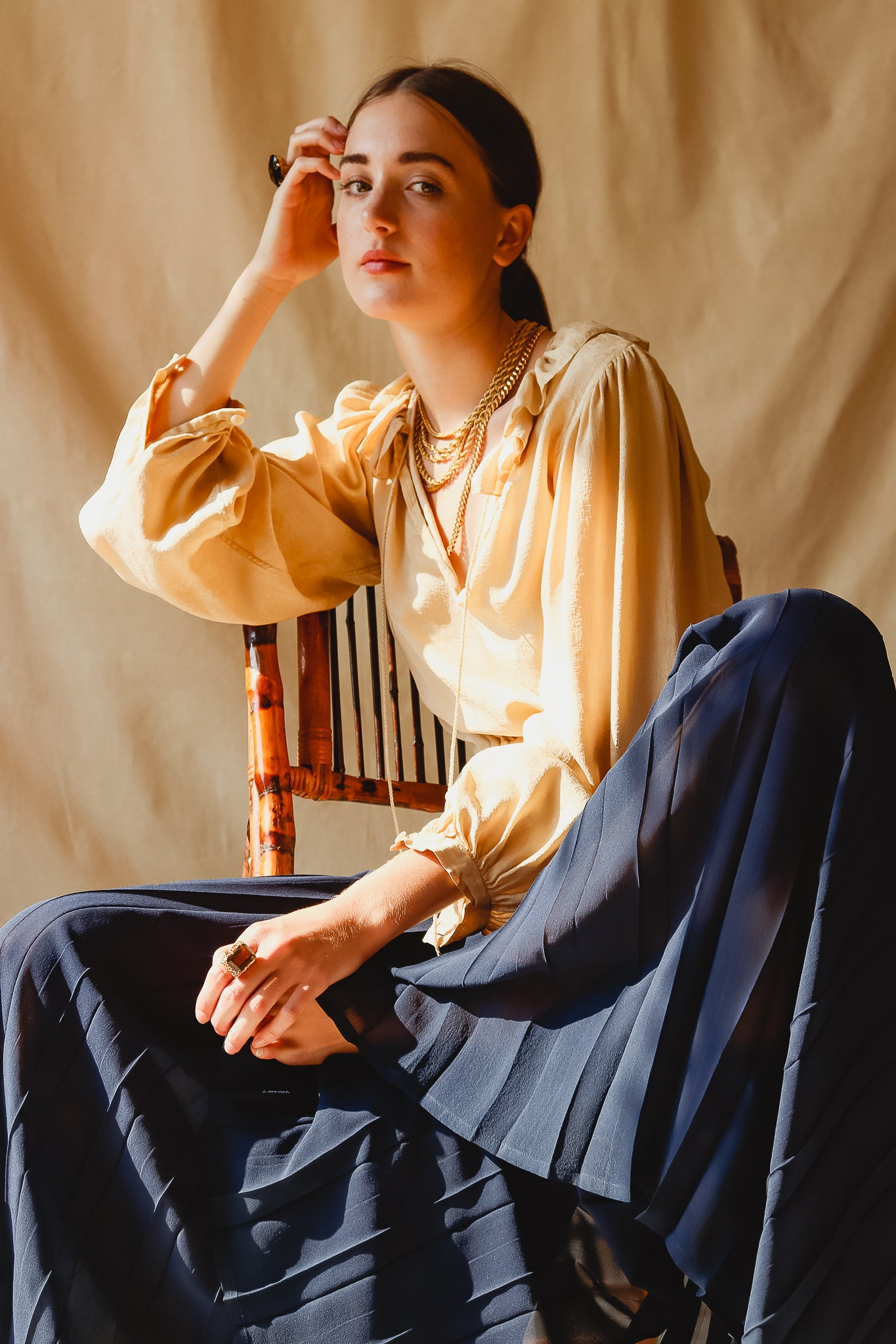 Recess Vintage Consignment LA Girl sitting in beige YSL Blouse & Mila Schon Sheer Palazzo Pants