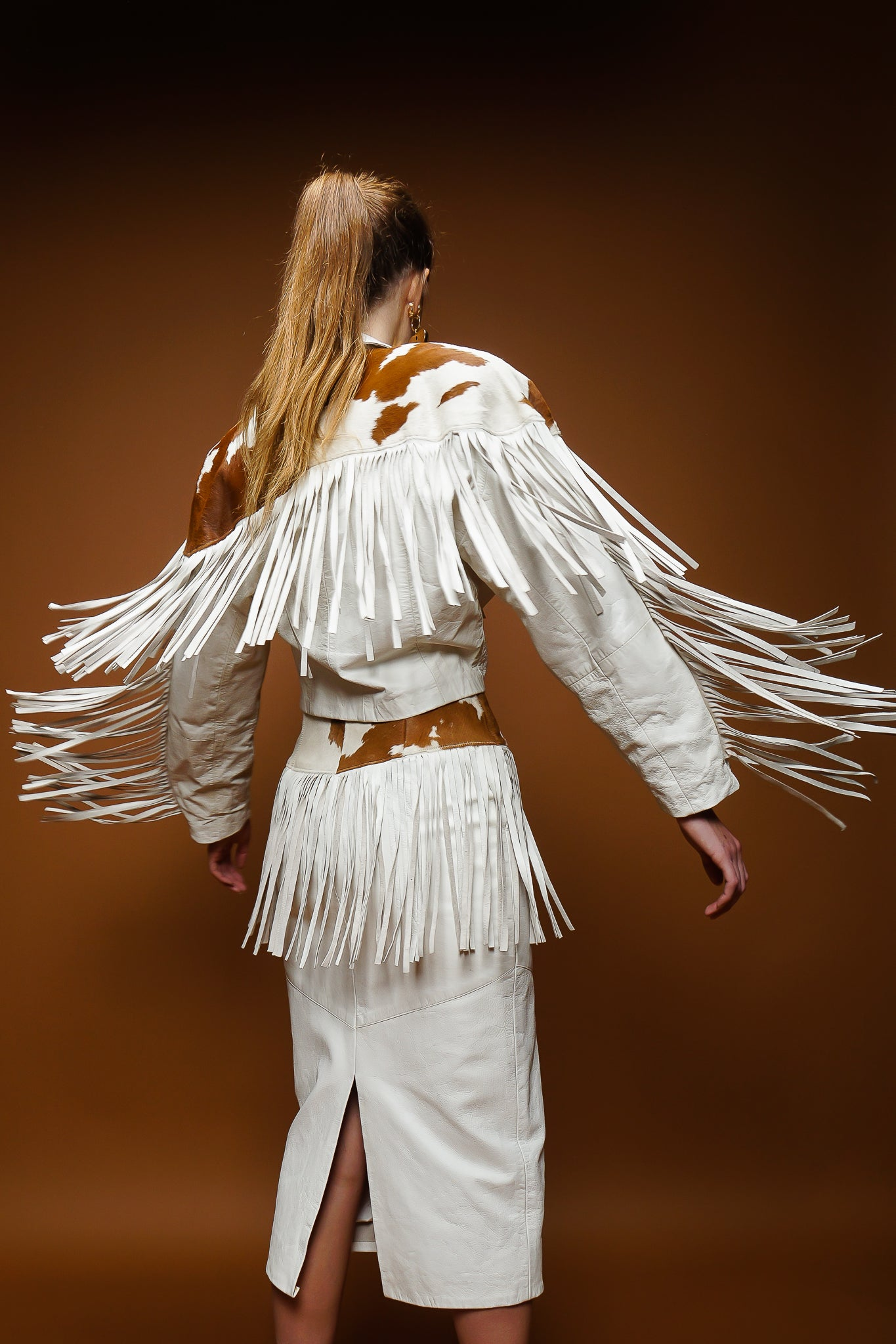 girl in Dali Melame white leather haircalf fringe jacket & skirt set on brown at Recess Los Angeles