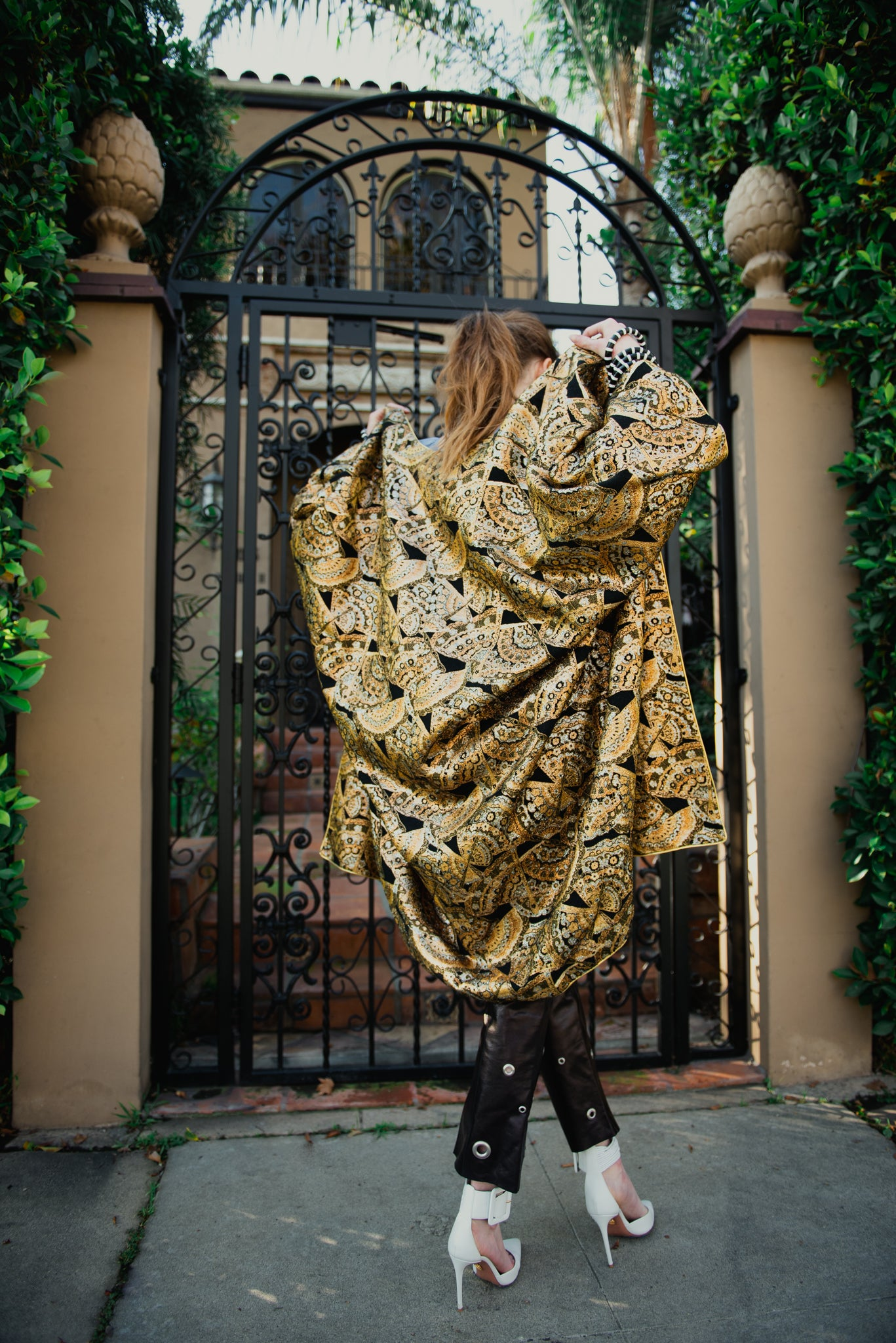 Girl in gold brocade Anthony Muto Cocoon coat leather pants & white heel front of gate