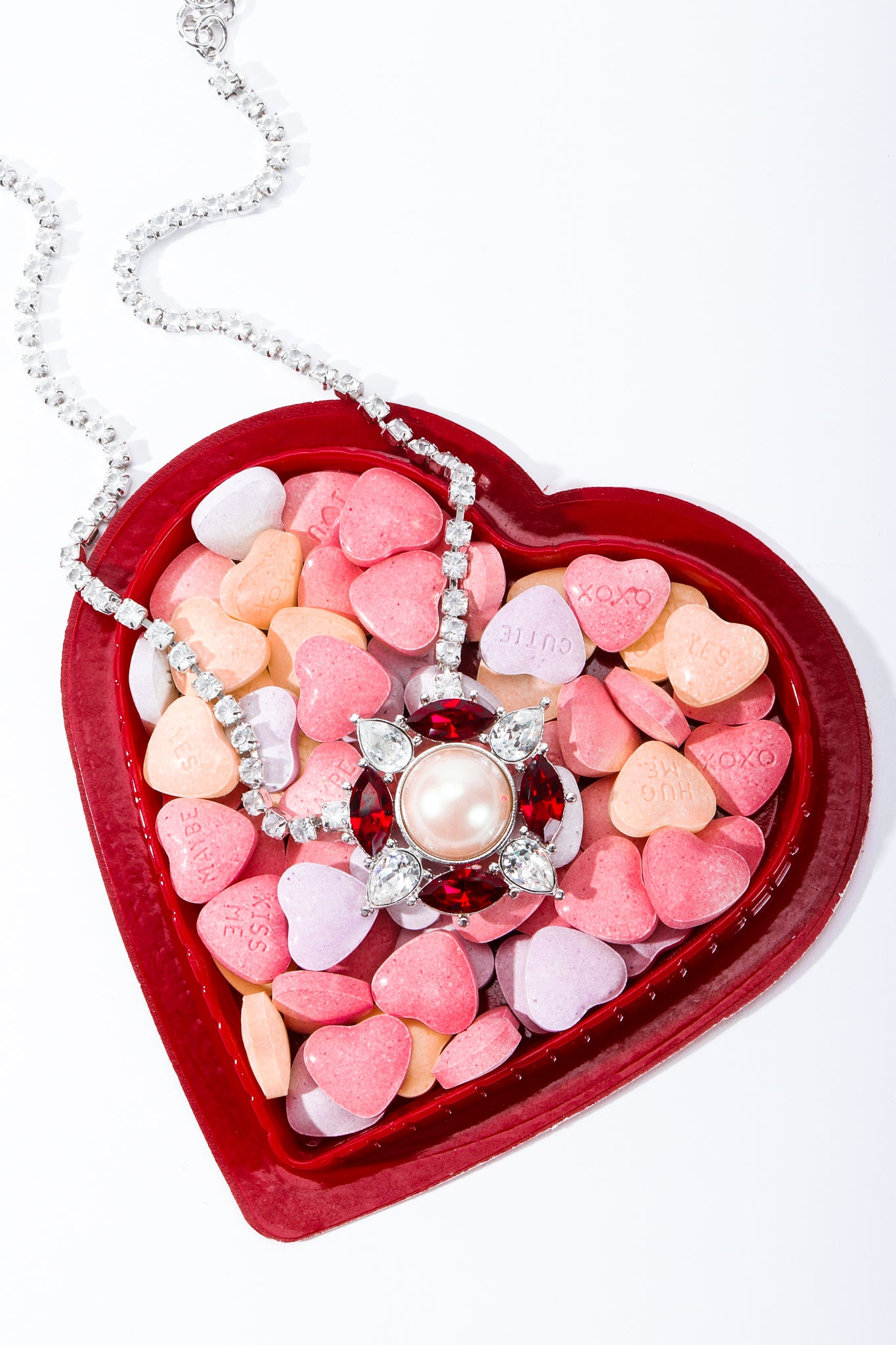 YSL faux ruby lifesaver necklace on heart shaped box of candy hearts