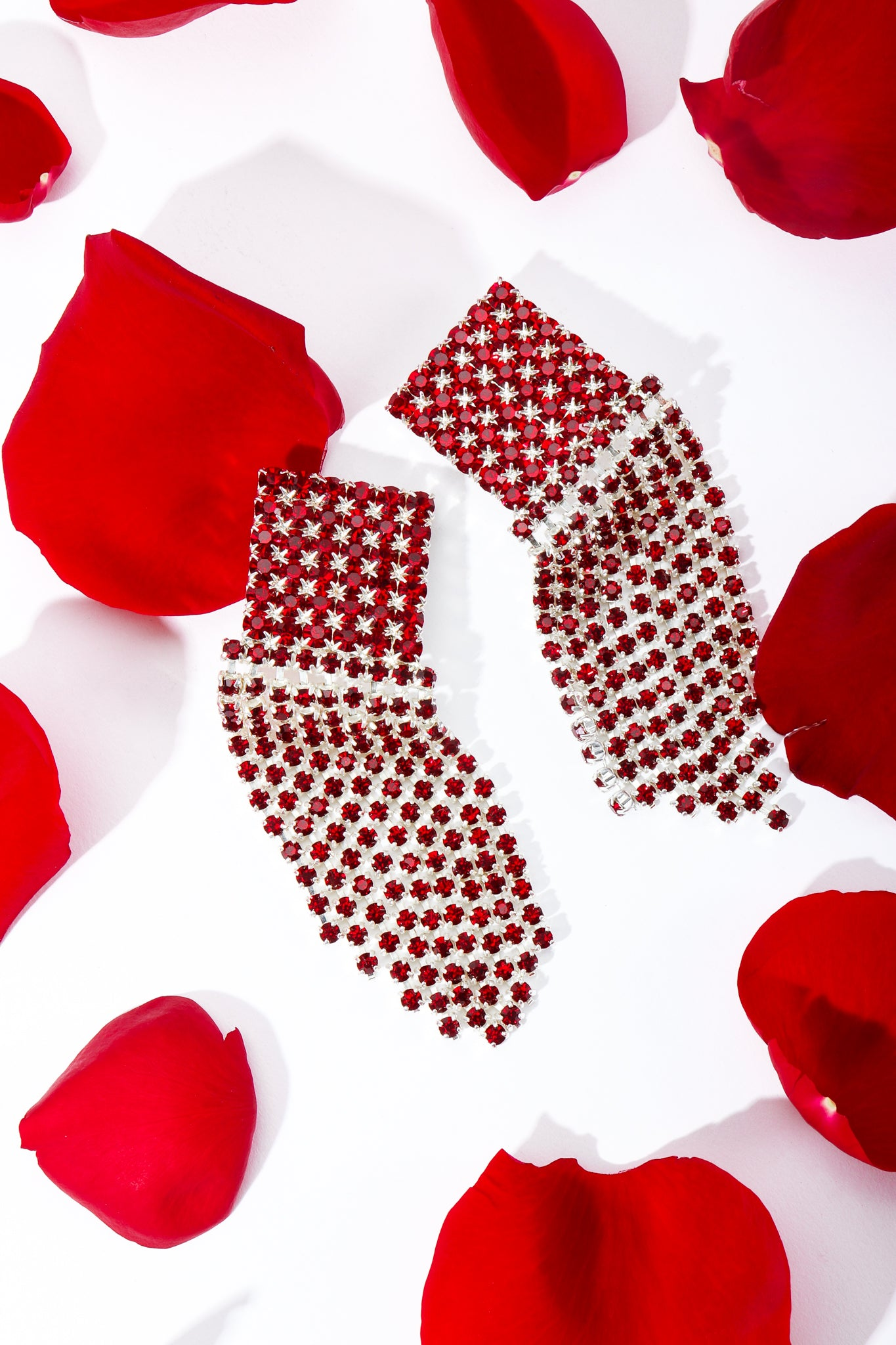 Red Rhinestone Fringe Heart Earrings with red rose petals at Recess Los Angeles