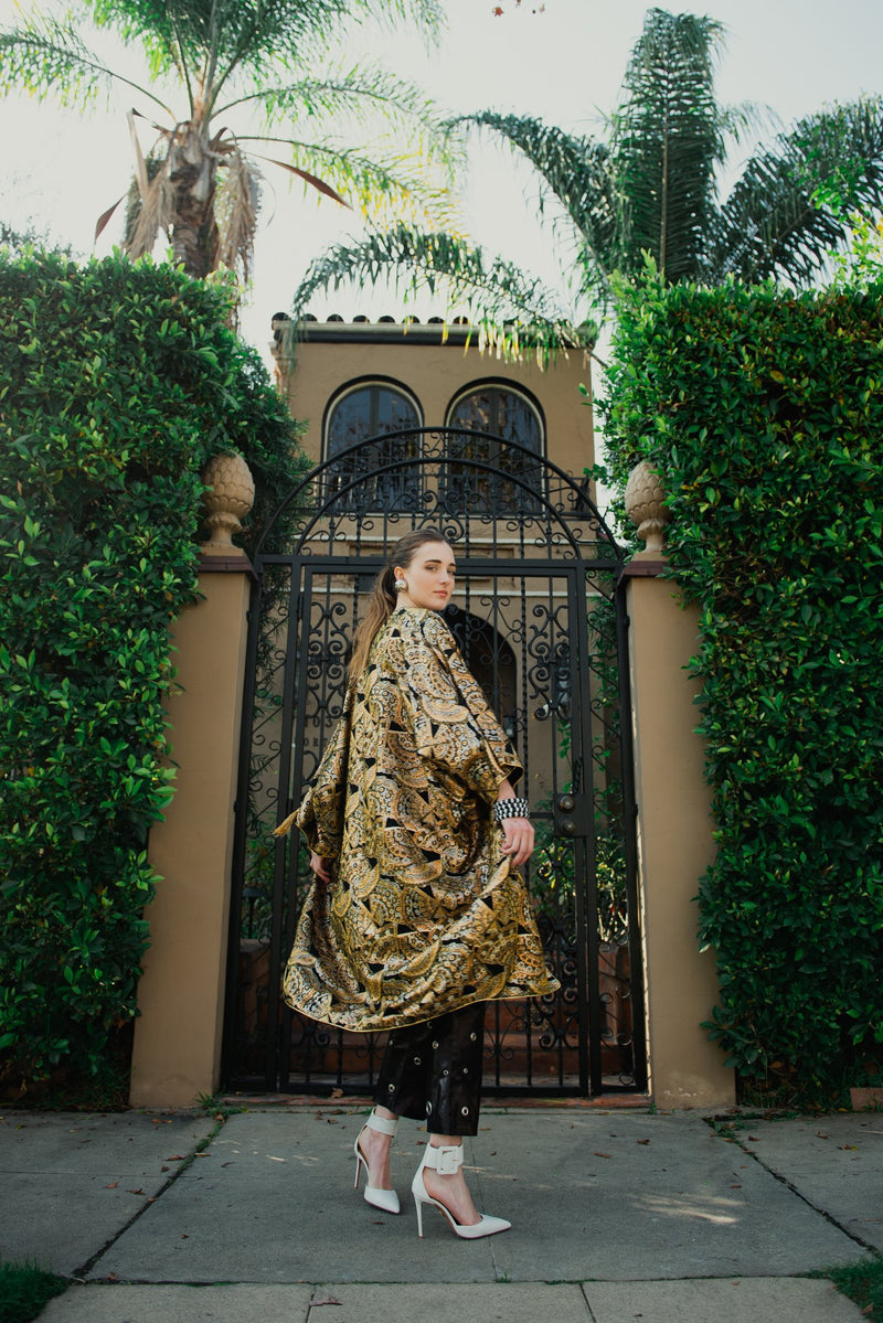 Girl in vintage Anthony Muto gold cocoon coat from Recess in front of gate